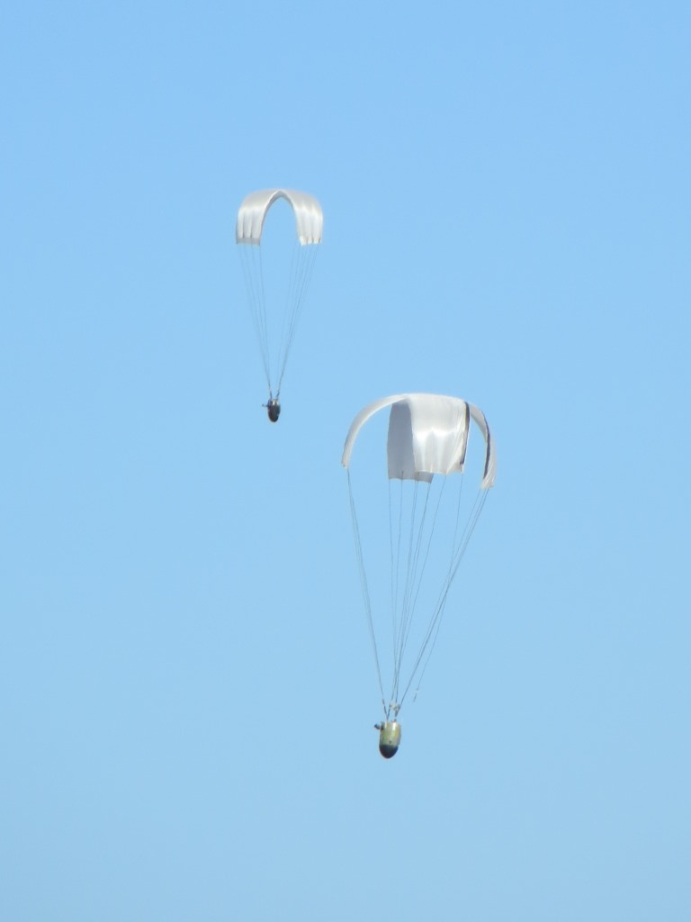 Figure B. Double airdrop of cross-type parachute systems (a), and two systems rigged for deployment (b).