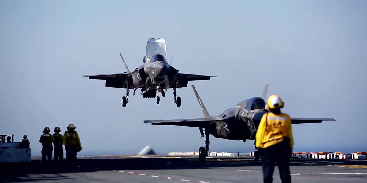 Image of fighter jets landing on an aircraft carrier deck.