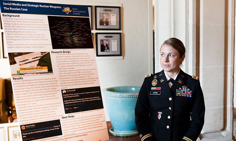 U.S. Army Maj. Trisha Wyman prepares to present during the annual Defense Analysis Research Week.